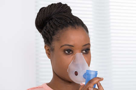Close-up Of Young African Woman Using Oxygen Mask 写真素材