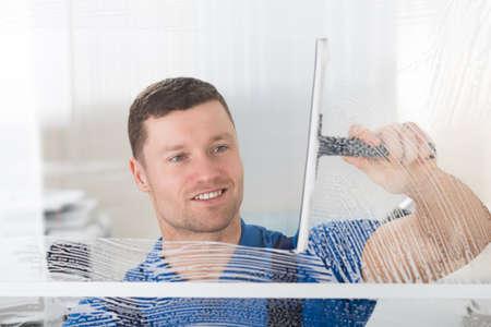 Sonriente mediados de limpieza sud jabón en la ventana de cristal con la escobilla de goma trabajador adulto