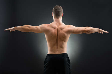Rear view of muscular man standing arms outstretched against black background