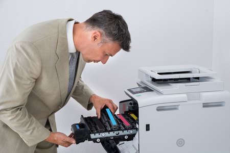cartridges: Mature businessman fixing cartridge in photocopy machine at office Stock Photo