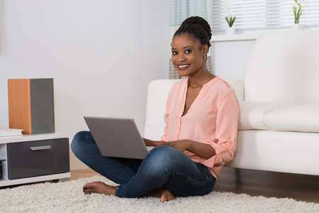 using computer: Portrait Of A Young African Woman Smiling While Using Laptop In Living Room