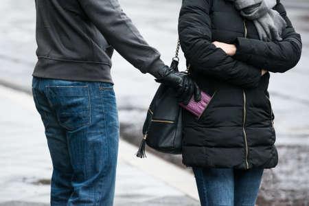 delito: Sección media de embrague joven ladrón que roba Hombre de la chaqueta de la mujer en la calle durante el invierno Foto de archivo