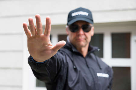 security: Confident security guard making stop gesture outside building Stock Photo