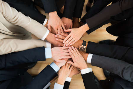 Directly above shot of business team stacking hands in office Imagens
