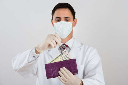 surgery costs: Midsection of male surgeon removing banknote from wallet against white background Stock Photo