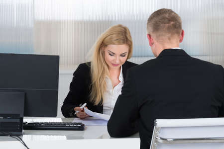 job application: Young businesswoman interviewing job applicant at desk in office