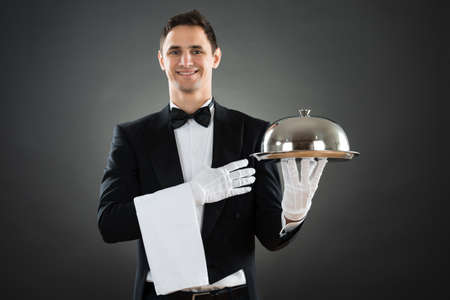 hospitality staff: Portrait of happy waiter with tray and towel standing against gray background Stock Photo