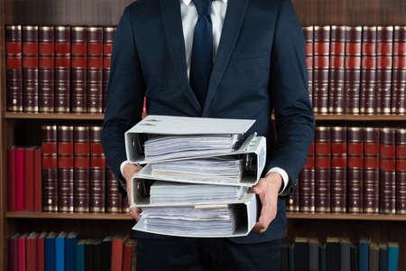 orden judicial: Sección media de abogado de sexo masculino que lleva pila de carpetas de anillas en la sala de audiencias