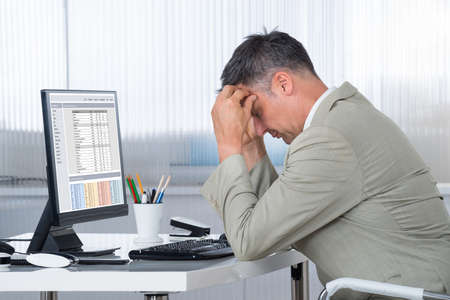 Side view of accountant suffering from headache at desk in office