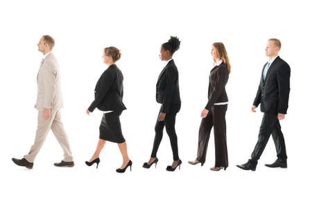 Full-length zijaanzicht van business team lopen in de rij tegen een witte achtergrond