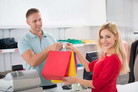 Portrait of happy female customer taking shopping bags from salesman at counter in store Stock Photo