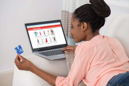 room card: Young African Woman Shopping Online With Debit Card Stock Photo