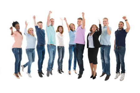 Full length portrait of creative business team celebrating success against white background Stock Photo