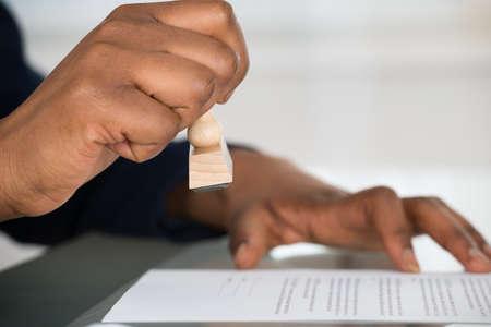 sello: Primer plano de la mano de una persona que estampa En el Formulario de Contrato Aprobado