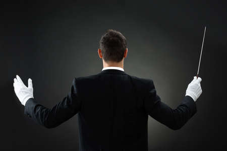 choral: Rear view of male music conductor holding baton against gray background Stock Photo