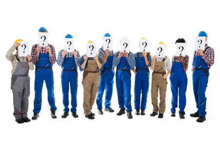 tradesmen: Full length of construction workers hiding faces with question mark signs against white background