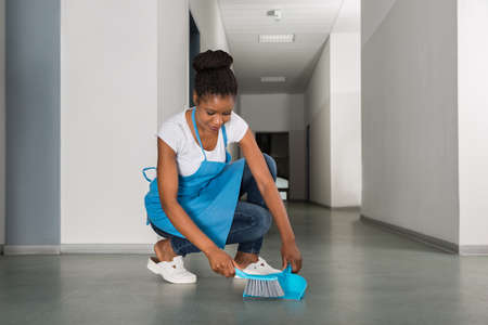 office cleanup: Young African Woman Sweeping Floor With Whisk Broom