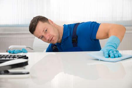 Mitte der erwachsenen männlichen Pförtner Reinigung Schreibtisch mit Schwamm im Büro