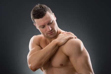 shoulder problem: Mid adult muscular man suffering from shoulder pain against black background