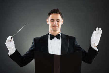 choral: Portrait of smiling music conductor holding baton against gray background Stock Photo