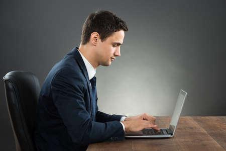 Zijaanzicht van zakenman met laptop op het bureau tegen een grijze achtergrond