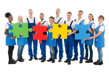 Cleaning team: Portrait of confident janitors holding jigsaw pieces while standing in row against white background