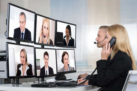 web conference: Business people having conference call with multiple computer screens at table in office Stock Photo