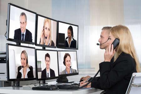 La gente de negocios que tienen conferencia telefónica con múltiples pantallas de ordenador a la mesa en la oficina