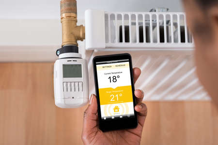 cool gadget: Close-up Of A Persons Hand Adjusting Temperature On Thermostat Using Cellphone Stock Photo