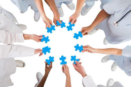 직접 흰색 배경에 대해 모이 블루 퍼즐 조각을 들고 의료 팀의 샷 위 스톡 콘텐츠