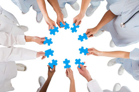 Directly above shot of medical team holding blue jigsaw pieces in huddle against white background Foto de archivo