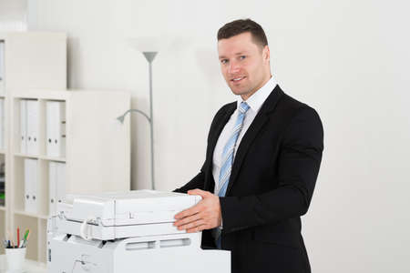 copier: Portrait of confident businessman standing by photocopy machine in office
