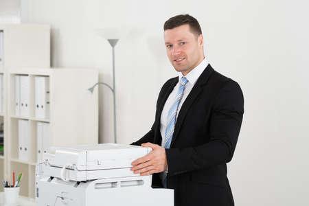 fotocopiadora: Retrato de confianza empresario de pie de máquina fotocopiadora en la oficina