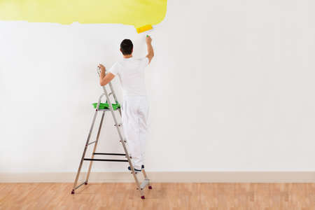 yellow walls: Rear view of young man painting wall with yellow paint roller at home Stock Photo