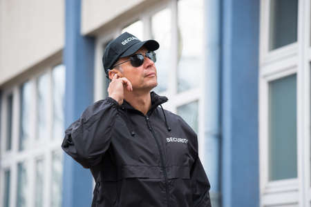 talkie: Mature security guard wearing sunglasses while using mobile phone outside building Stock Photo