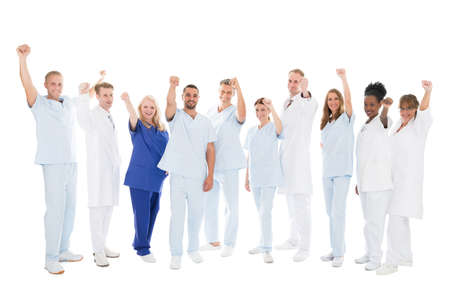 Full length portrait of multiethnic medical team standing with arms raised against white background