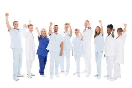 Retrato de cuerpo entero de equipo médico multiétnica de pie con los brazos en alto contra el fondo blanco Foto de archivo - 50245672