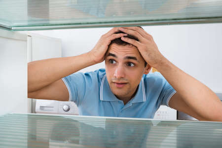 looking into: Amazed young man looking into empty refrigerator at home Stock Photo