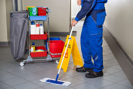office equipment: Low section of male janitor with broom cleaning office corridor