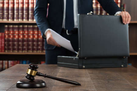 courtroom: Midsection of lawyer putting documents in briefcase with gavel at desk in courtroom Stock Photo