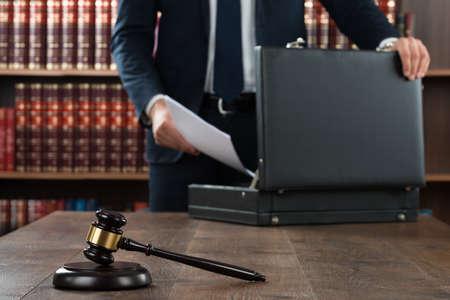 Mittlerer Teil des Rechtsanwalts Dokumente in Aktenkoffer mit Hammer am Schreibtisch im Gerichtssaal setzen