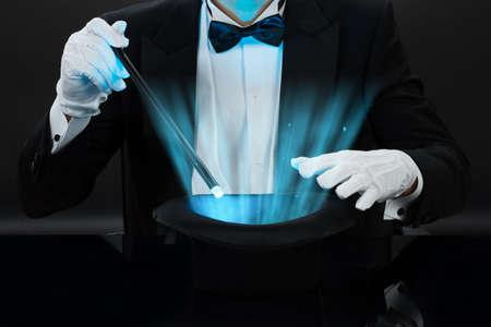黒の背景に照らされた帽子の上の魔法の杖を握っている手品師の中央部