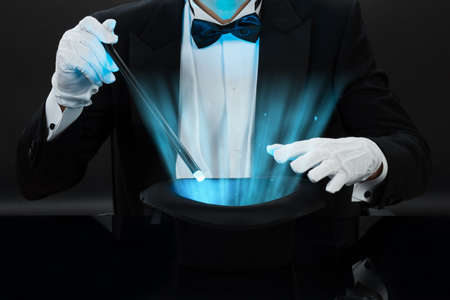 Buik van goochelaar bedrijf toverstokje over verlichte hoed tegen zwarte achtergrond