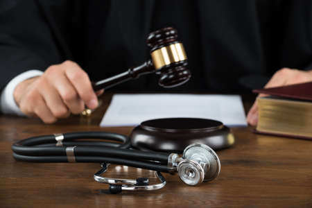 Midsection of judge striking mallet with stethoscope at desk in courtroom