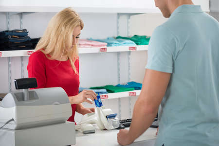Young female cashier using credit card while standing with male customer at counter in store