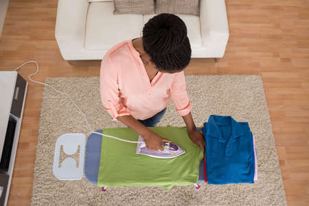 Hot house: High Angle View Of Woman Ironing Clothes On Iron Board