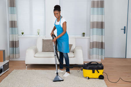 american house: Smiling Young African Woman Cleaning Carpet With Vacuum Cleaner