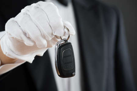 hospitality staff: Midsection of waiter holding car key against gray background Stock Photo