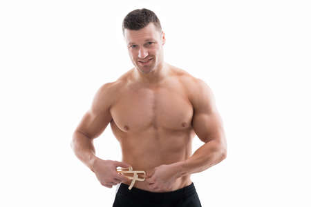 Mid adult muscular man measuring fats with caliper against white background