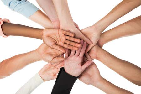 manos juntas: Directamente debajo de tiro del equipo creativo de negocio manos acumulando contra el fondo blanco
